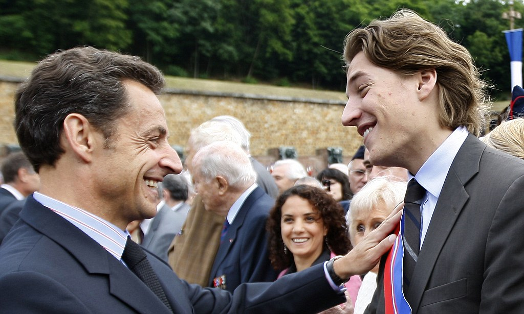 FILE - This June 18, 2009 file photo shows French President Nicolas Sarkozy, left, shaking hands with his son Jean Sarkozy during a commemorative ceremony at the Mont Valerien memorial in Suresnes, west of Paris. Critics are questioning a bid by President Nicolas Sarkozy's 23-year-old son for a job overseeing France's premier business district. Jean Sarkozy, a municipal official, is the key candidate to become chairman of EPAD, the agency that oversees billions of euros in contracts and business at La Defense on the western outskirts of Paris. (AP Photo/Chales Platiau, pool, File)