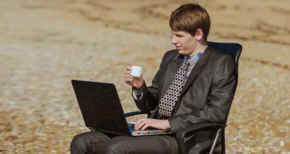 Молодой бизнесмен с чашкой кофе и ноутбуком сидит в кресле на песчаном берегу